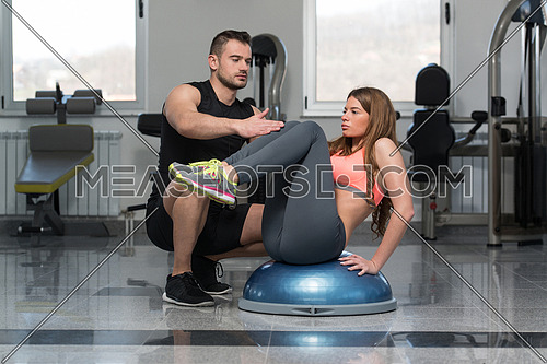 Personal Trainer Showing Young Woman How To Train On Bosu Abs Exercise In A Health And Fitness Concept