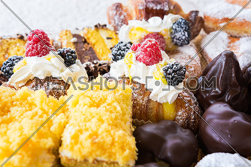 In the pictured typical italian pastries with cream,choccolate,rasperry and blackberry with various forms.