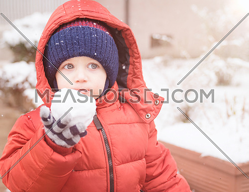Newborn boy while snowing looks towards the emptiness, holding in his hand a snowball, covered with red winter jacket and woolen hat, close-up.