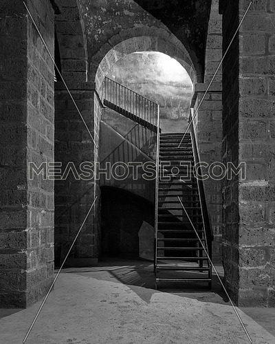Black and white of dark abandoned underground passage with stone bricks columns and metal staircase, Medieval Cairo, Egypt