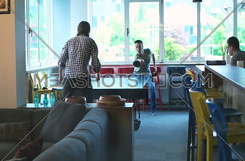 business people paying table tennis in startup office