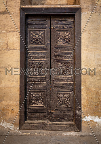 Wooden aged grunge door and stone bricks wall, al Zaher Barquq Mosue, Medieval Cairo, Egypt