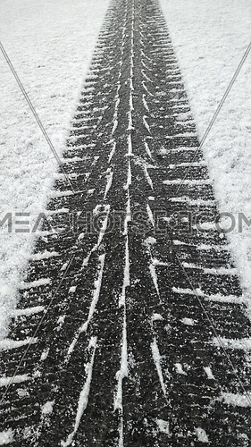 Close up black winter tire tread footprint on white snow of road surface, high angle view, diminishing perspective