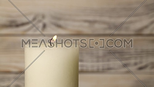 Close up one white candle trembling flame over background of old brown wooden planks wall, off-center, fired up with lighter, burning and blown out