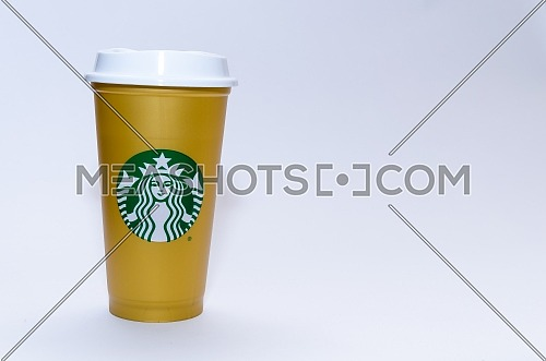 A colored Starbucks cup in Golden color. December 2018 in Cairo - Egypt.