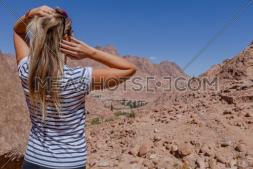 Long shot for a female tourist from behind exploring Sinai Mountain for wadi Freij at day.