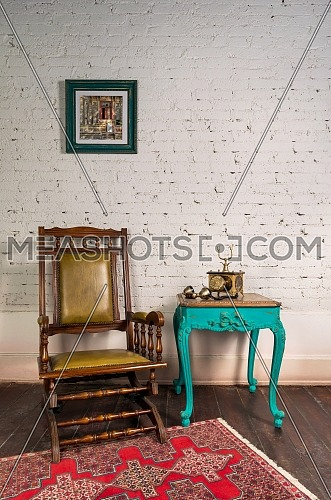Classical wooden rocking chair, antique golden telephone set on top of green wooden vintage table and background of white bricks wall with hanged painting and parquet floor with red carpet