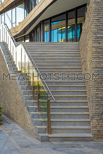Stone staircase and railing leading to entrance of contemporary city building with glass mirrored walls