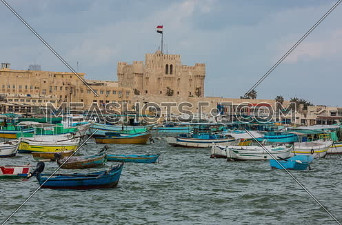 Fixed Long Shot outside Citadel of Qaitbay shows fishing boats at day