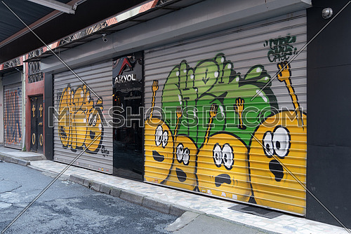 Istanbul, Turkey - April 18, 2017: Closed shop exterior with metal rolling doors painted with colorful graffiti at Hoca Tahsin Street, Karakoy district