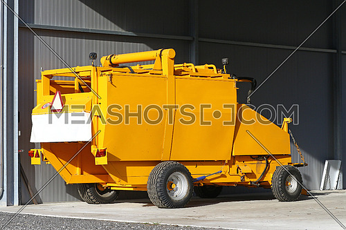 Yellow agricultural tow compactor for baling grass