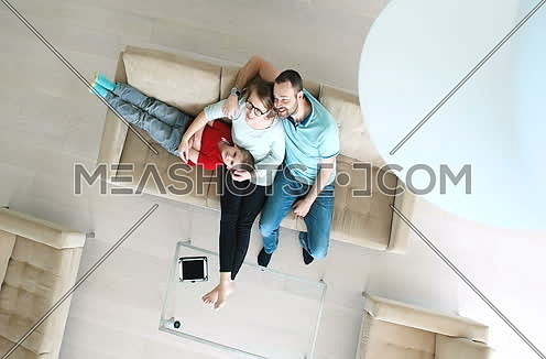 Top View Of Parents And Their Little Kids Lying On sofa At Home And watching tv