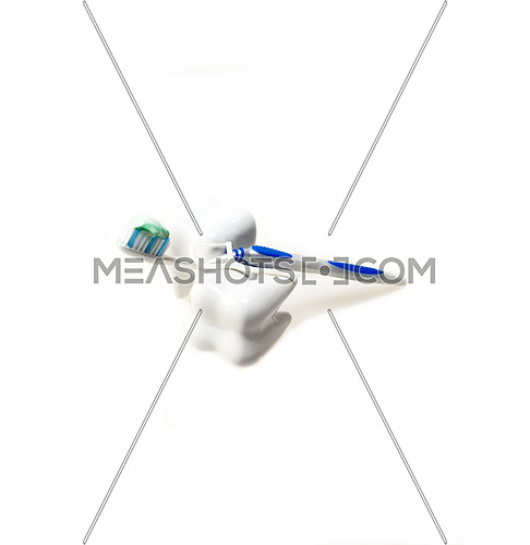 two fake teeth with brush and floss closeup isolated on white