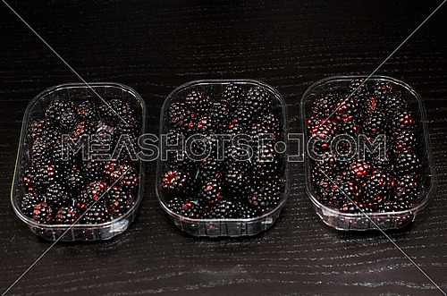3 boxes of fresh blackberries on a black wooden background