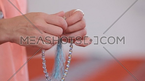 Close up for Young Muslim girl's Hands with rosary praying on white background.