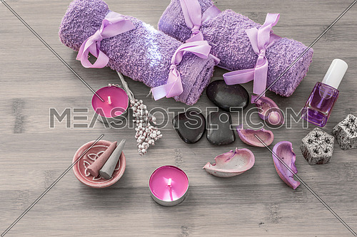 Spa concept. Rocks,candle and bath white towels on wooden background