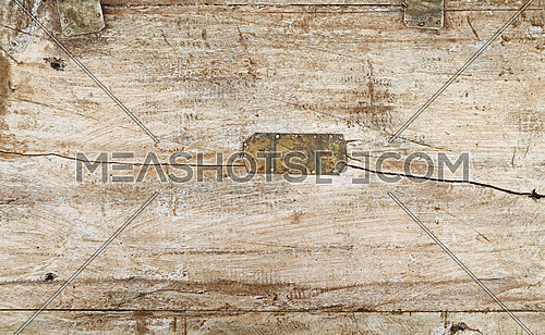 Grunge background texture of white painted wood with dark brown and black dirty stains, scratches, cracks and nailed tin metal patch