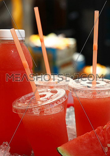 Fresh squeezed red ripe watermelon juice in plastic cups with straws and bottle on ice in retail market stall display, close up, low angle view