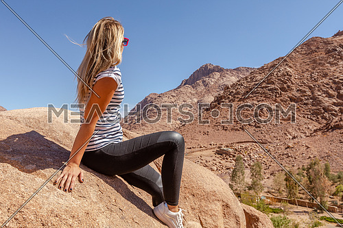long shot for a female tourist stiing on a rock explore Sinai Mountain for wadi Freij at day.