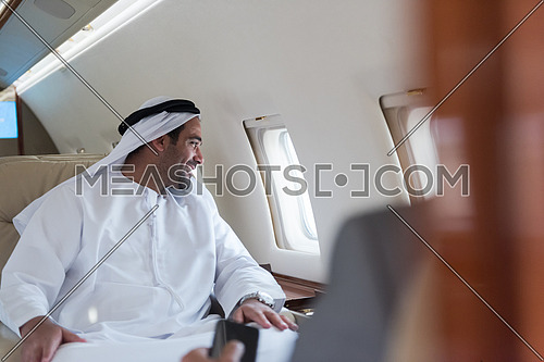 Portrait of a young middle eastern successful man in traditional clothes who enjoys sitting in private jet