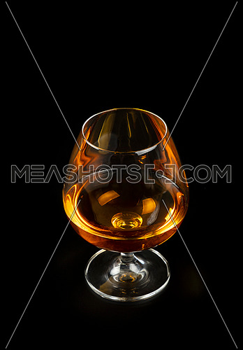 Close up one glass of cognac or brandy isolated on black background, high angle view