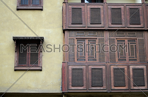 Front side of an old Islamic style  building with a wooden windows and balconies