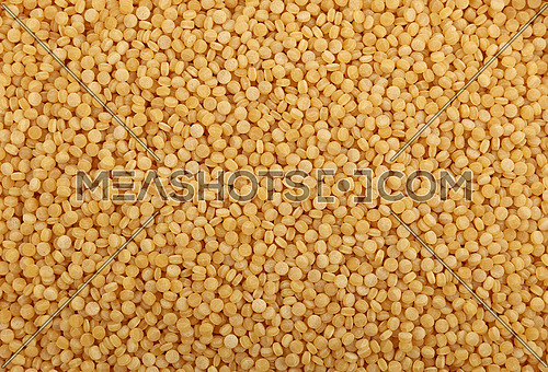 Traditional ptitim pasta (Palestinei or pearl couscous) close up pattern background, elevated top view