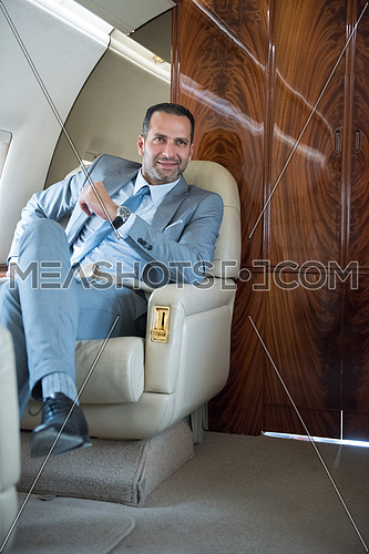 Portrait of a young middle eastern successful businessman who enjoys sitting in private jet