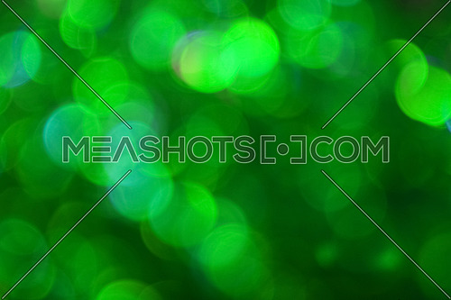 Colorful vivid green bokeh defocused blurred lights and sparkles abstract background