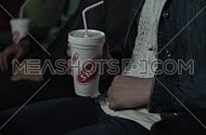 Close up shot for young man hand holding soda at the movies.