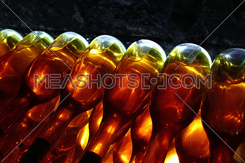 Close up rows of backlit white wine glass bottles stacked aging in winery cellar