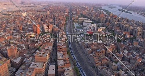 Aerial shot for the city beside the River Nile while Metro's stooped in Cairo at sunset
