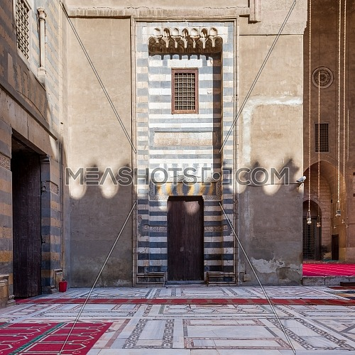Wall with striped black and white marble decorations, wooden grunge door and window at the courtyard of historic public mosque of Sultan Hassan, Cairo, Egypt
