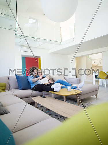 Young couple on the sofa watching television together in their luxury home