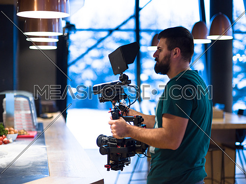 videographer recording while Professional team cooks and chefs preparing meal at busy hotel or restaurant kitchen