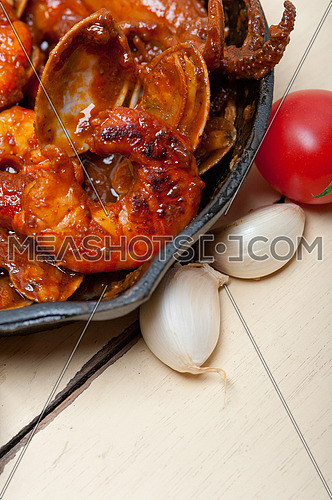 fresh seafood stew prepared on an iron skillet ove white rustic wood table