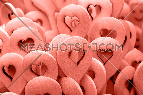 Close up coral pink color toned handmade rustic wooden cooking spoons with carved heart shape at retail market stall display