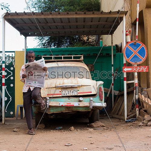 """A Sudanese taxi driver reading the morning paper and parked beside a """"No Parking"""" sign on 15th of July 2015"""