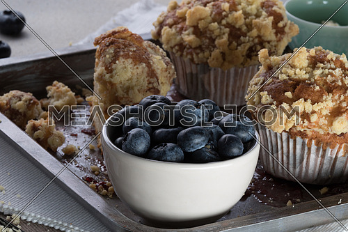 Muffins with crumbs and blueberry in a white bowl on a tray moist with jam