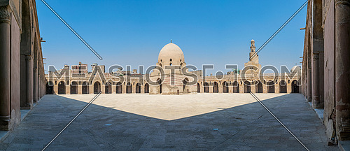 Panorama of the courtyard of Ibn Tulun public historic mosque, Cairo, Egypt, with the ablution fountain and the minaret