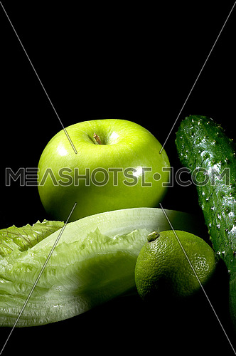 group of green vegetables and fruits over black background