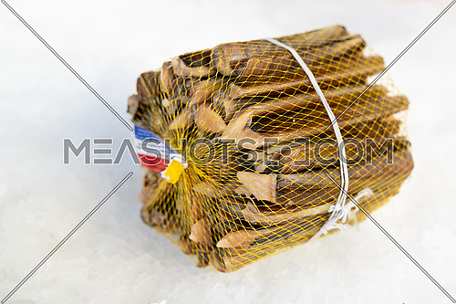 """Stack of Solen marginatus, common name """"grooved razor shell"""" (Italian: cannolicchio),sold at market on ice, seafood."""