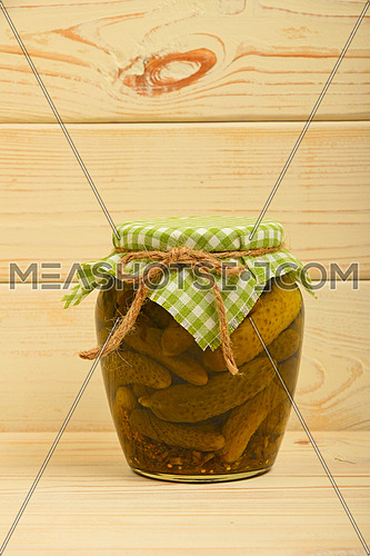 One glass jar of homemade pickled cucumbers with green checkered textile top decoration at beige painted vintage wooden surface