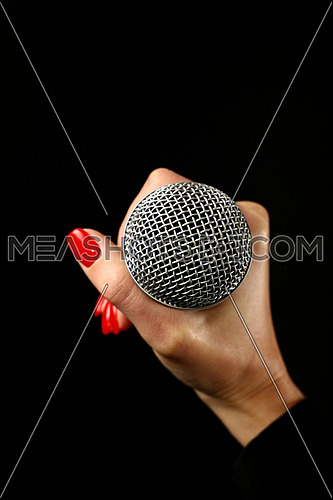 Woman hand with red nails holding microphone isolated on black background