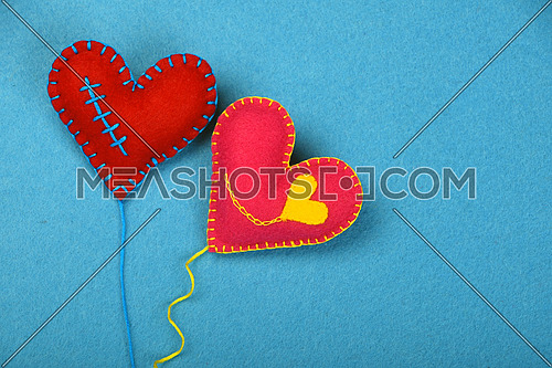 Felt craft and art, two handmade stitched toy hearts with yellow thread, red and pink on blue background, top view
