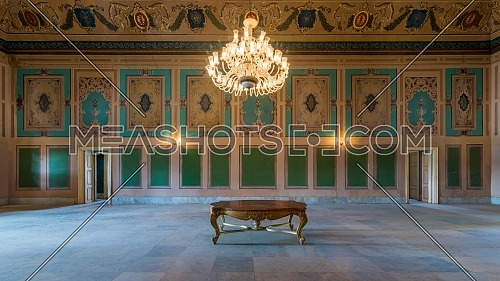 Royal era historic Manasterly Palace with beautiful elegant carved frames on green wall with ornate borders, floral decorated ceiling, chandelier, and marble floor, Cairo, Egypt