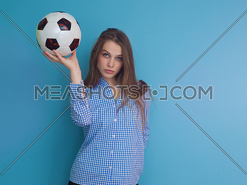 Portrait of a beautiful positive young woman while playing with a soccer ball isolated on blue background