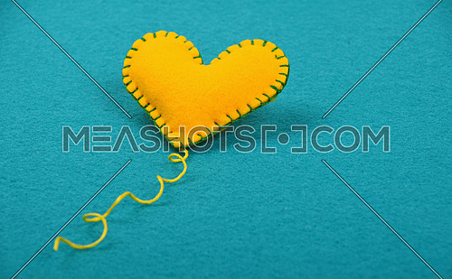 Felt craft and art, one handmade yellow stitched toy heart with thread on blue background, low angle view