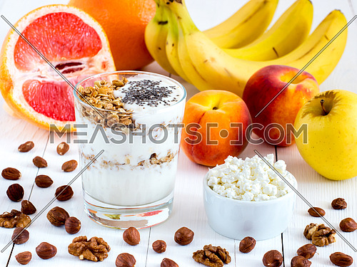 Healthy breakfast: cottage cheese and yogurt with muesli and chia seeds, fruits and nuts on white wooden background. Dieting, healthy lifestyle concept meal