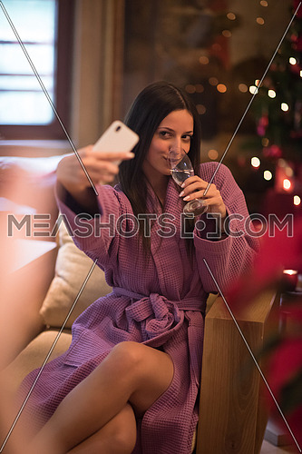 people, and relaxation concept   beautiful young woman in bath robe drinking champagne and doing selfy at spa over holidays lights background